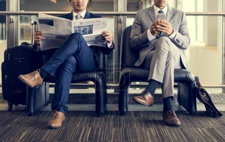 Businessmen reading newspaper and using smartphone