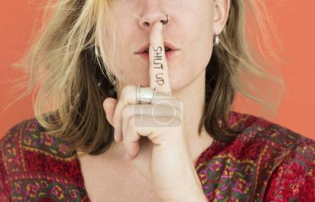 blonde Woman holding finger at mouth
