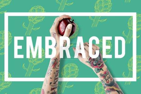 Tattooed woman hand holding apple