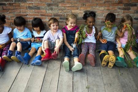 Group of kindergarten kids siting near wall