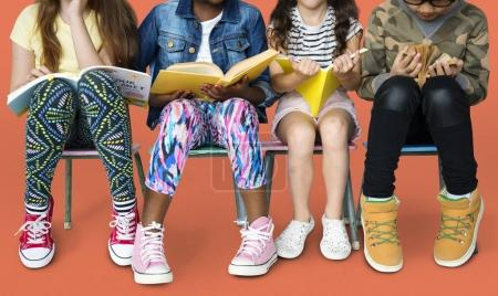 children sitting on chairs with books