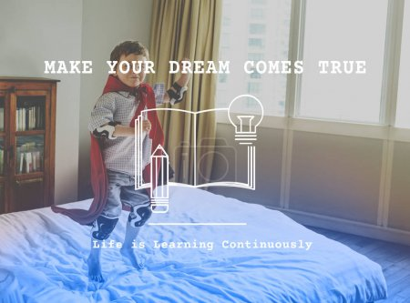 Boy in Superhero costume jumping on bed