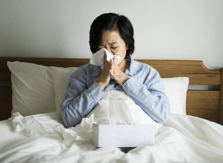 sick Asian woman in bed