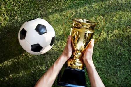 man holding award near Football