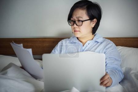 woman working on a laptop in bed