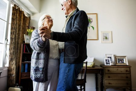 Senior couple dancing together ta home