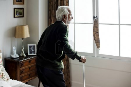 elderly Indian man at the nursing home looking to window