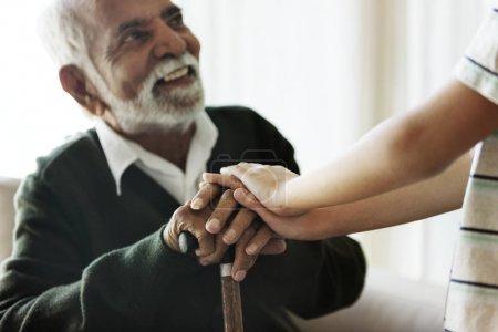 Close Up Of Senior Man's Hands Holding Walking Cane