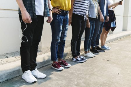 Young adult friends standing near wall, youth culture concept