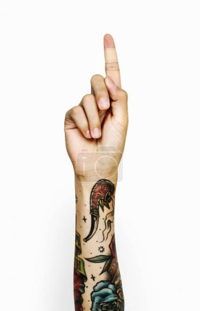 human hand with tattoos gesturing one finger up