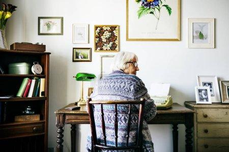 Foto de Senior mujer escrito en máquina de escribir antigua - Imagen libre de derechos
