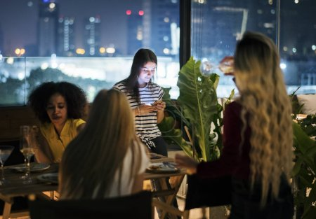 Young woman using a smartphone at a dinner night having no interaction with friends addiction concept