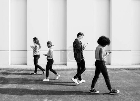 Young adults using smartphones as they are walking outdoors, black and white
