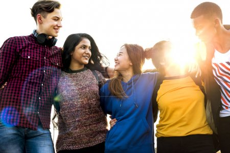 Group of school friends outdoors arms around one another togetherness and community concept
