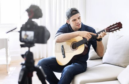 Male blogger recording music related broadcast at home