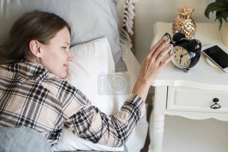 Woman reaching hand to turn off the alarm