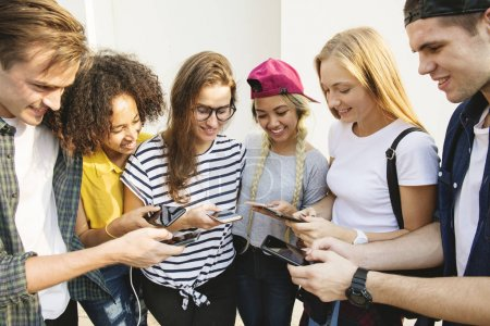 Young adult friends using smartphones together outdoors, youth culture concept