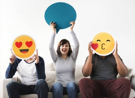 Group of diverse friends sitting on couch with emoticon internet and connection concept