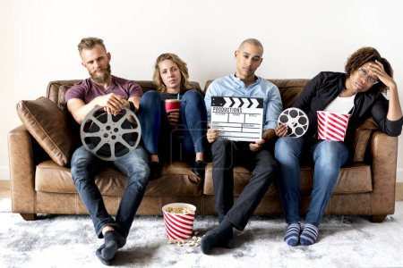 Sad group of friends holding movie and film objects