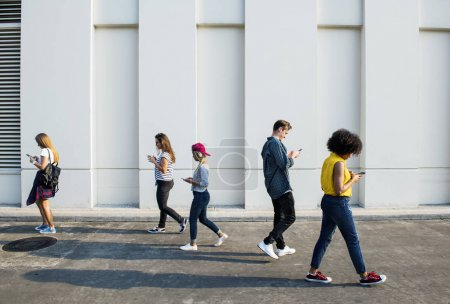 Young adults using smartphones as they are walking outdoors