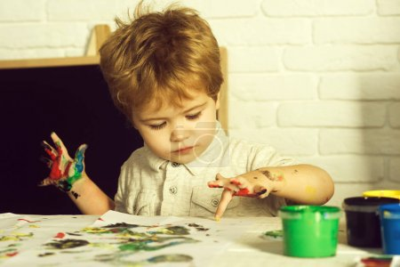 Child fingerprint art. Drawing for children, little artists. Finger paints, free time for toddler. ?ice talented boy draws a yellow paint in children's center in master class of art. Creative kid boy