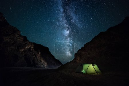 Photo for Night rocky ravine. starry sky with bright milky way. an illuminated tent - Royalty Free Image