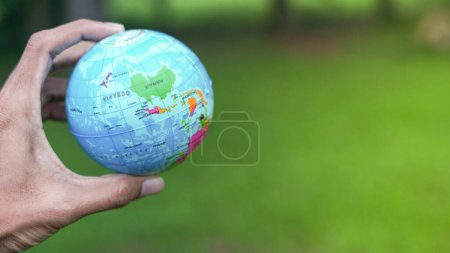 Travel concept.Close up shot of a man's hand holding a world globe.Copy Space.