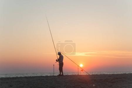 Fisherman standing on a pier at dawn sky background with sun ray
