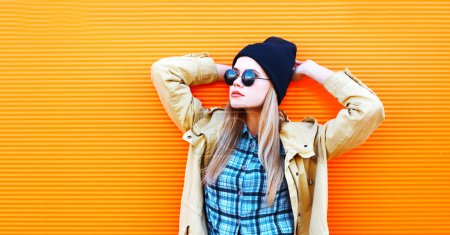 Photo for Fashion portrait blonde woman in black sunglasses and hat on a colorful orange background empty copy space - Royalty Free Image
