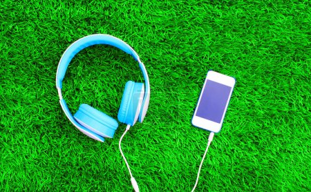 Headphones connected to white smartphone on a green grass textur