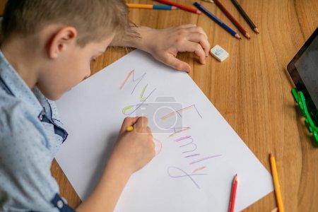 Photo pour Plan rapproché. Ma famille. Les mains des enfants dessinent un tableau, il montre papa, maman, frères et sœurs. Gros plan coeur dénote l'amour - image libre de droit