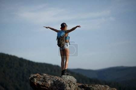 Hiking happy woman with backpack standing on rock with raised ha