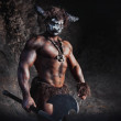 The bodyart man angry minotaur with axe in cave