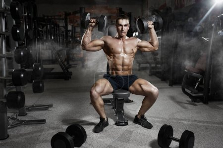 Photo for Athlete muscular bodybuilder in gym training biceps with dumbbell - Royalty Free Image