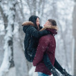 Beautiful young couple having fun in the snowy cit...