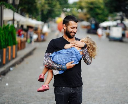 Photo for Cute little girls sleeping in her fathers arm in the street - Royalty Free Image