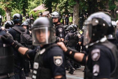 Photo pour Les policiers de la brigade sont en alerte le long de la rue de la ville. La police se suit, s'accrochant au dos suivant . - image libre de droit