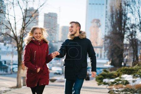 Photo pour Couple heureux posant pour la caméra dans la rue en hiver - image libre de droit