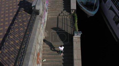 Photo pour 7 mai 2019, Ukraine, Kiev. Femme sportive courant sur un escalier en pierre, vue aérienne - image libre de droit