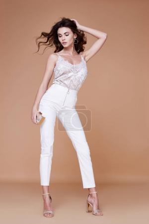 Photo for Beautiful young sexy woman with long wavy blond hair with bright evening make up perfect summer tan thin figure wear white silk blouse pants and high heels shoes perfect body shape diet accessory bag. - Royalty Free Image