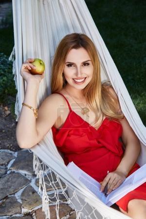 Photo pour Belle femme modèle avec de longs cheveux blonds se trouve dans un hamac détente repos expirer habillé en robe de soie rouge lit livre intéressant manger de la pomme dans le jardin bio nourriture été météo week-end parfait. - image libre de droit