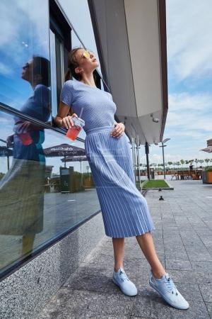 Photo pour Brunette sexy femme mode style rue look élégant promenade café restaurant date réunion entreprise succès porter robe bleue accessoire sac lunettes de soleil vêtements été collection boisson été limonade . - image libre de droit
