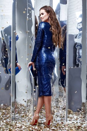 Photo for Sexy fashion beautiful lady pretty face makeup cosmetic brunette hairstyle beauty salon woman wear shine sequins blue dress party style fashion clothes New Year Christmas Saint Valentine's Day mirror. - Royalty Free Image
