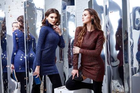 Photo pour Deux belles sexy femme amie porter luxe skinny robe bleue et rouge paillettes brillant style fête célébrer Nouvel An salon de beauté de Noël cheveux accessoire de maquillage bijoux modèle pose vêtements de mode . - image libre de droit