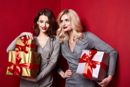 Photo pour Deux belles sexy jeune femme lumineuse soirée maquillage lèvres rouges longs cils moelleux tenir boîte cadeau vacances Nouvel An joie plaisir joyeux Noël fête fête fête Saint-Valentin petite amie. - image libre de droit