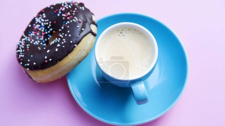 Photo for Blue cup of coffee with chocolate donut on pink tabl - Royalty Free Image