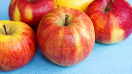 Photo for Closeup of red and yellow apples on blue background - Royalty Free Image