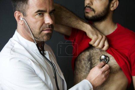Photo pour Beau médecin avec un stéthoscope à l'écoute des patients battements de coeur - image libre de droit
