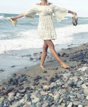 Photo for Woman in white dress holding her shoes walking barefoot on the beach - Royalty Free Image