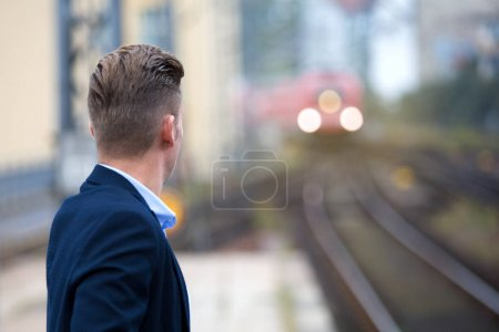 blond man waiting for the train